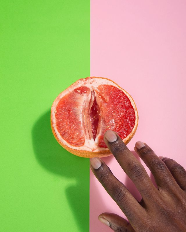 cropped hands of person touching grapefruit over two tone background