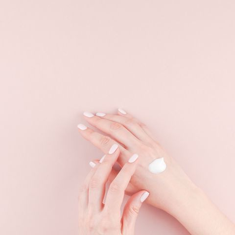 cropped hands of woman applying moisturizer pink background