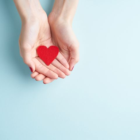 cropped hands of woman holding heart shape over blue background