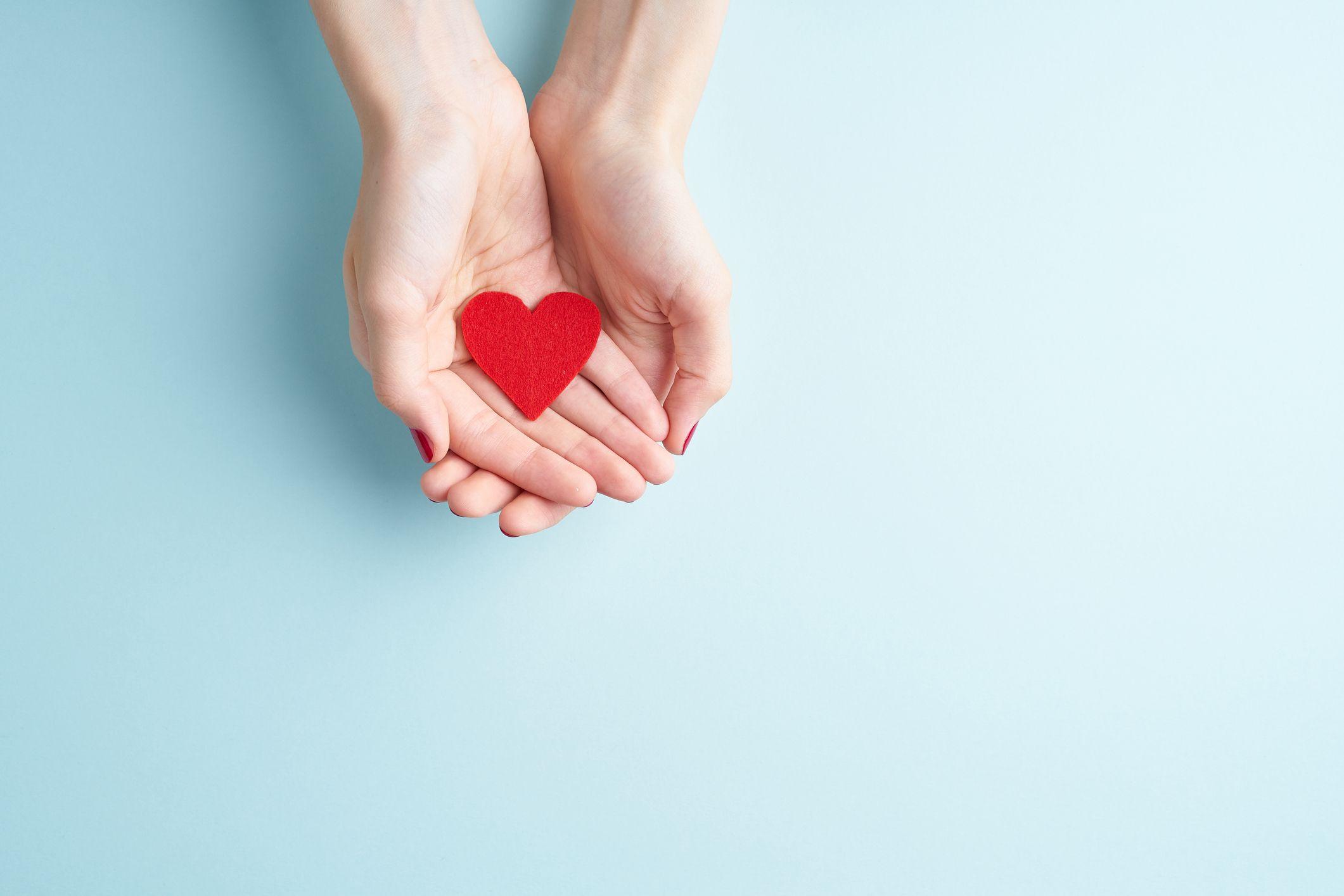 beskjærte hender av kvinne som holder hjerteform over blå bakgrunn