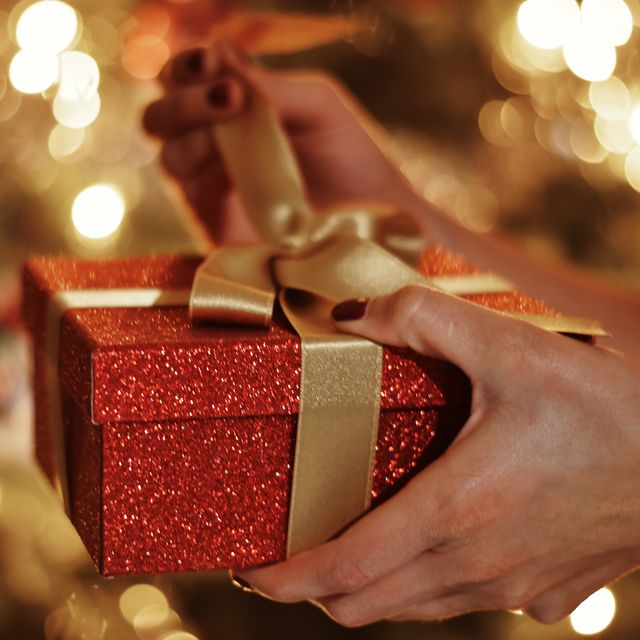 cropped hands of woman opening gift box against christmas lights