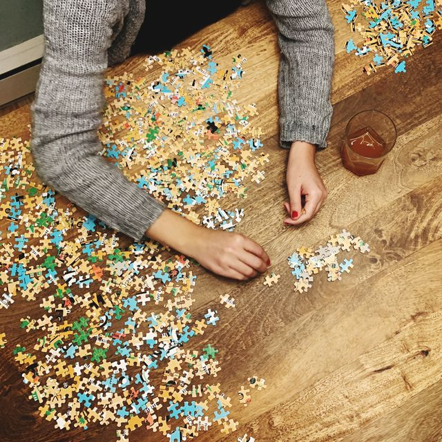 Cropped Hands Of Woman Playing Jigsaw Puzzle On Wooden Table At Home