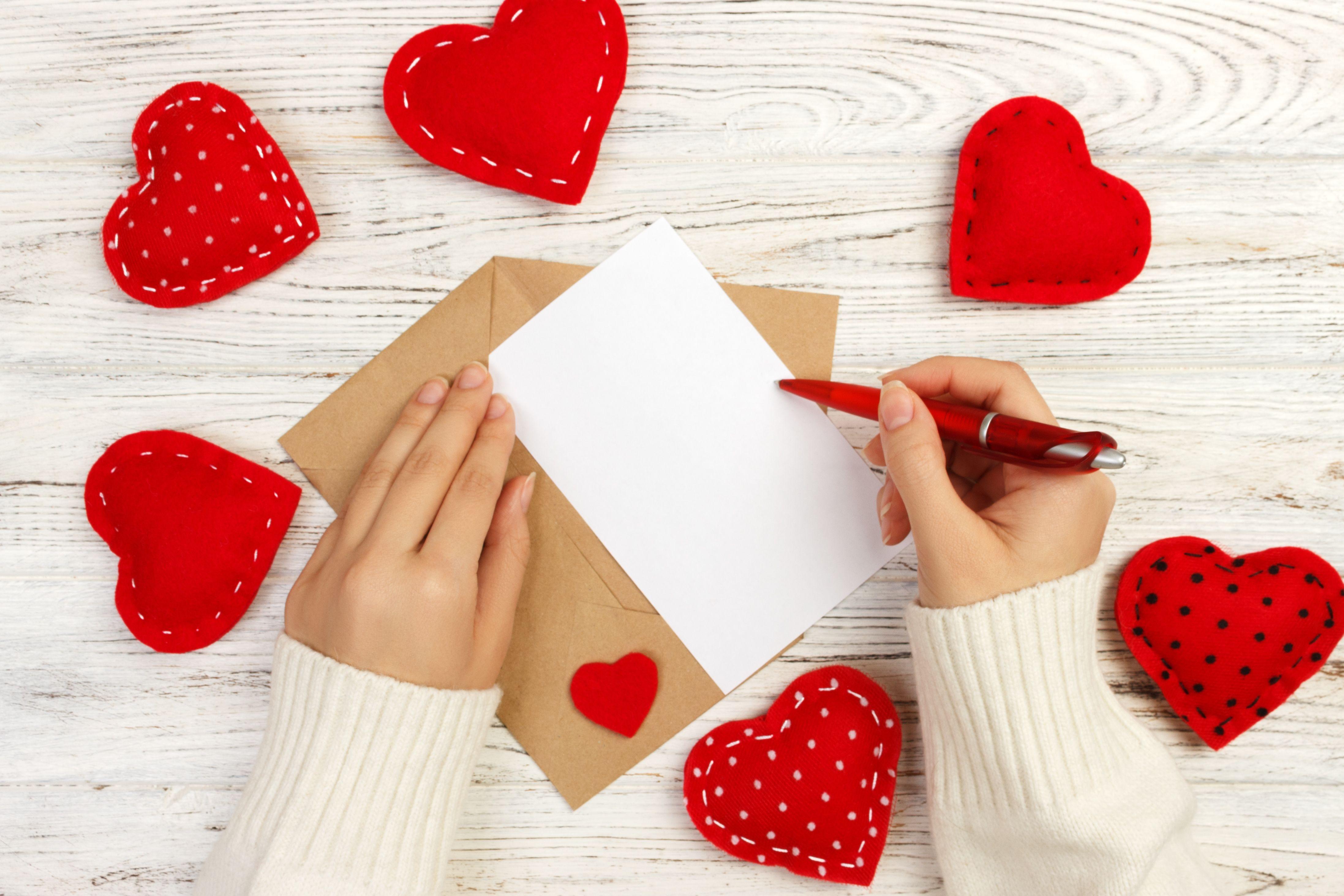 изрязани ръце на жена, пишеща на хартия на дървена маса