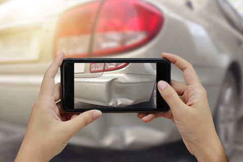 cropped hands photographing damaged car with smart phone