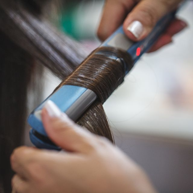 cropped image of beautician straightening hair of customer