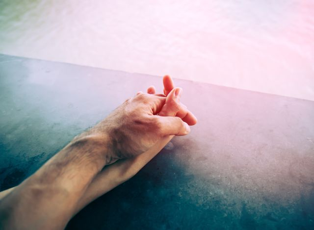 cropped image of couple holding hands by swimming pool