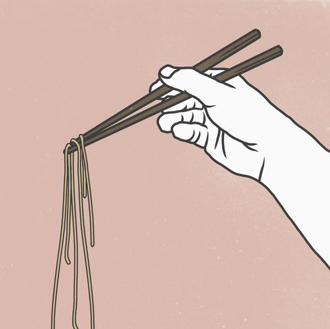 Cropped image of hand holding noodles with chopsticks against pink background
