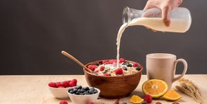 Cropped Image Of Hand Pouring Milk In Oatmeal On Table Against Gray Background