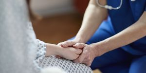 Cropped image of nurse holding patient's hand