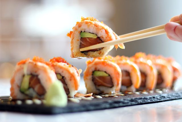 cropped image of person holding sushi at table
