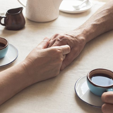 cropped image of senior couple holding hands and drinking coffee