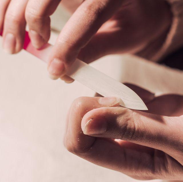 cropped image of woman filing nail at table