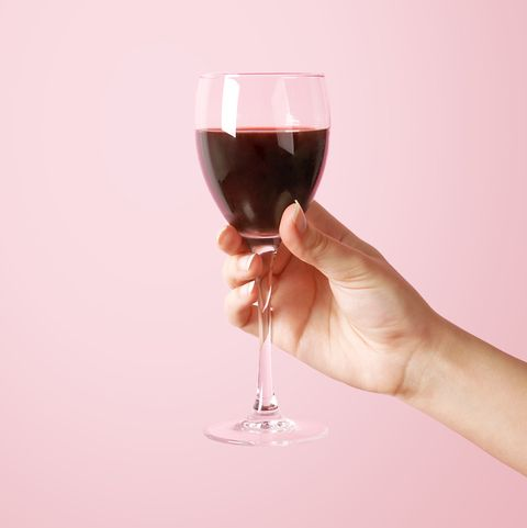woman holding wine glass on pink background