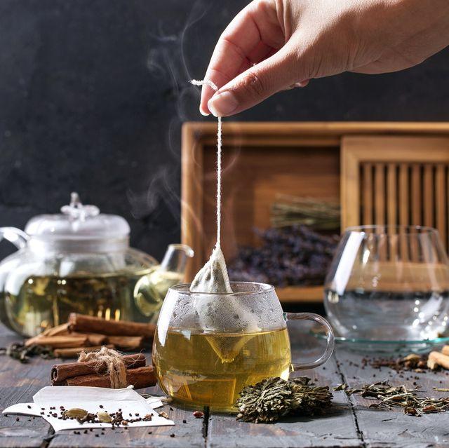 cropped image of woman preparing herbal tea on table