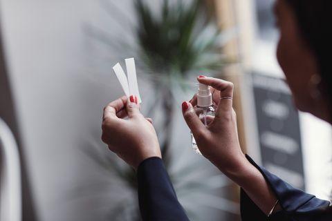 Cropped image of woman spraying perfume on litmus strips at workshop