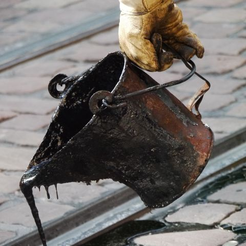 Cropped Image Of Worker Pouring Tar On Railroad Track
