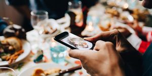 Cropped image of young man photographing food in plate at restaurant