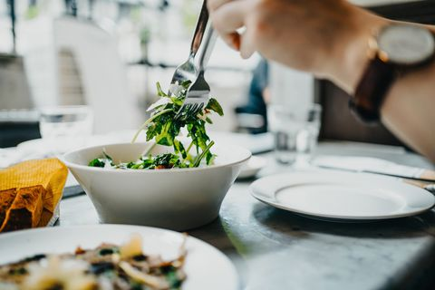 cropped shot of a woman's hand serving healthy salad on plate while having lunch in a restaurant