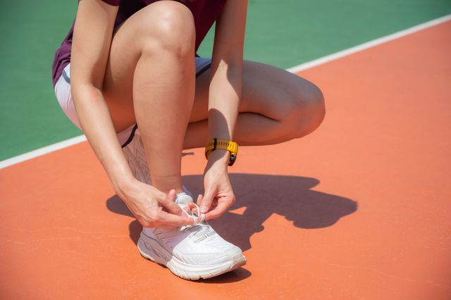 cropped shot of runner woman getting ready to tying shoelaces before running workout