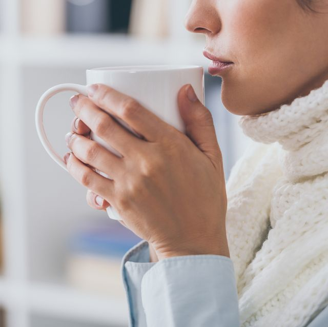 cropped shot of sick businesswoman in scarf drinking hot tea at office