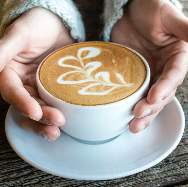 Cropped shot of someone hands holding a cup of latte coffee in the cafe shop.