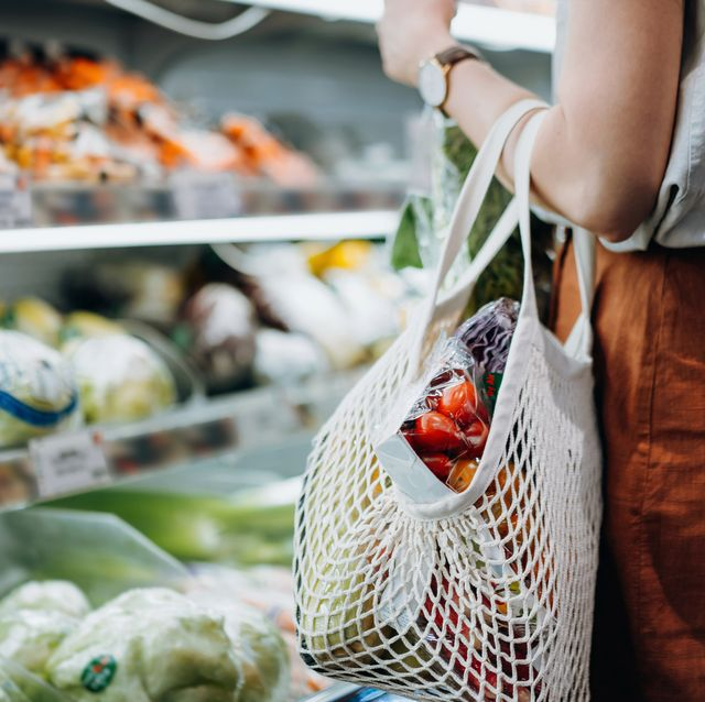 cropped shot of young asian woman shopping for fresh organic groceries in supermarket she is shopping with a cotton mesh eco bag and carries a variety of fruits and vegetables zero waste concept
