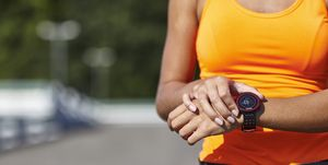 Cropped shot of young female runner setting smartwatch in parking lot