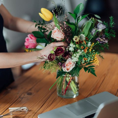 cropped shot of young woman arranging fresh flowers at home