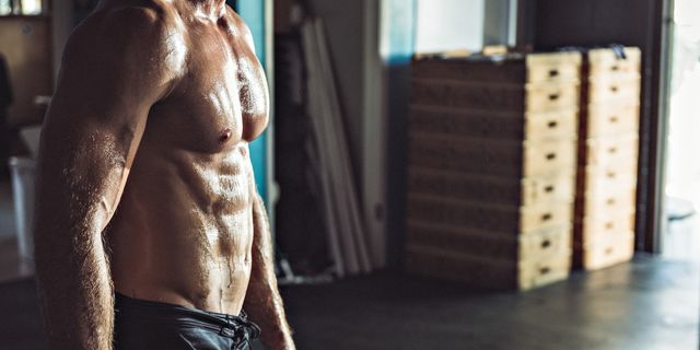 cropped view of muscular man in gym