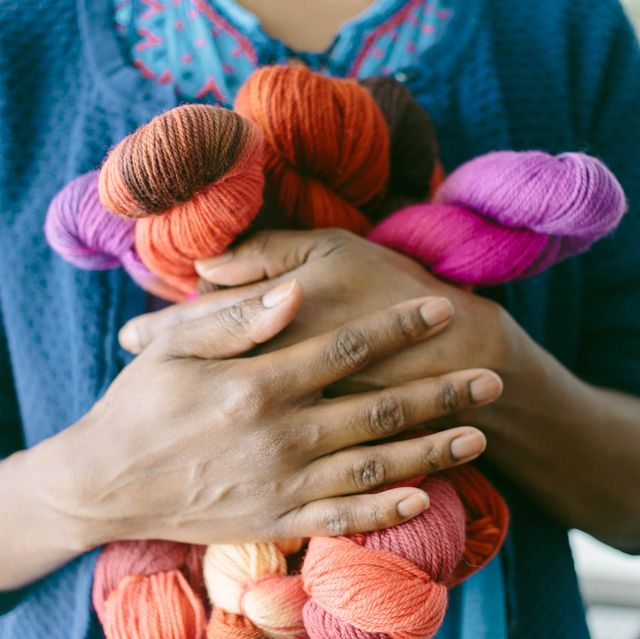 cropped view of woman clutching colorful yarn