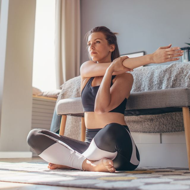 Cross-Body Shoulder Stretch. Woman at home does a warm up and stretch.