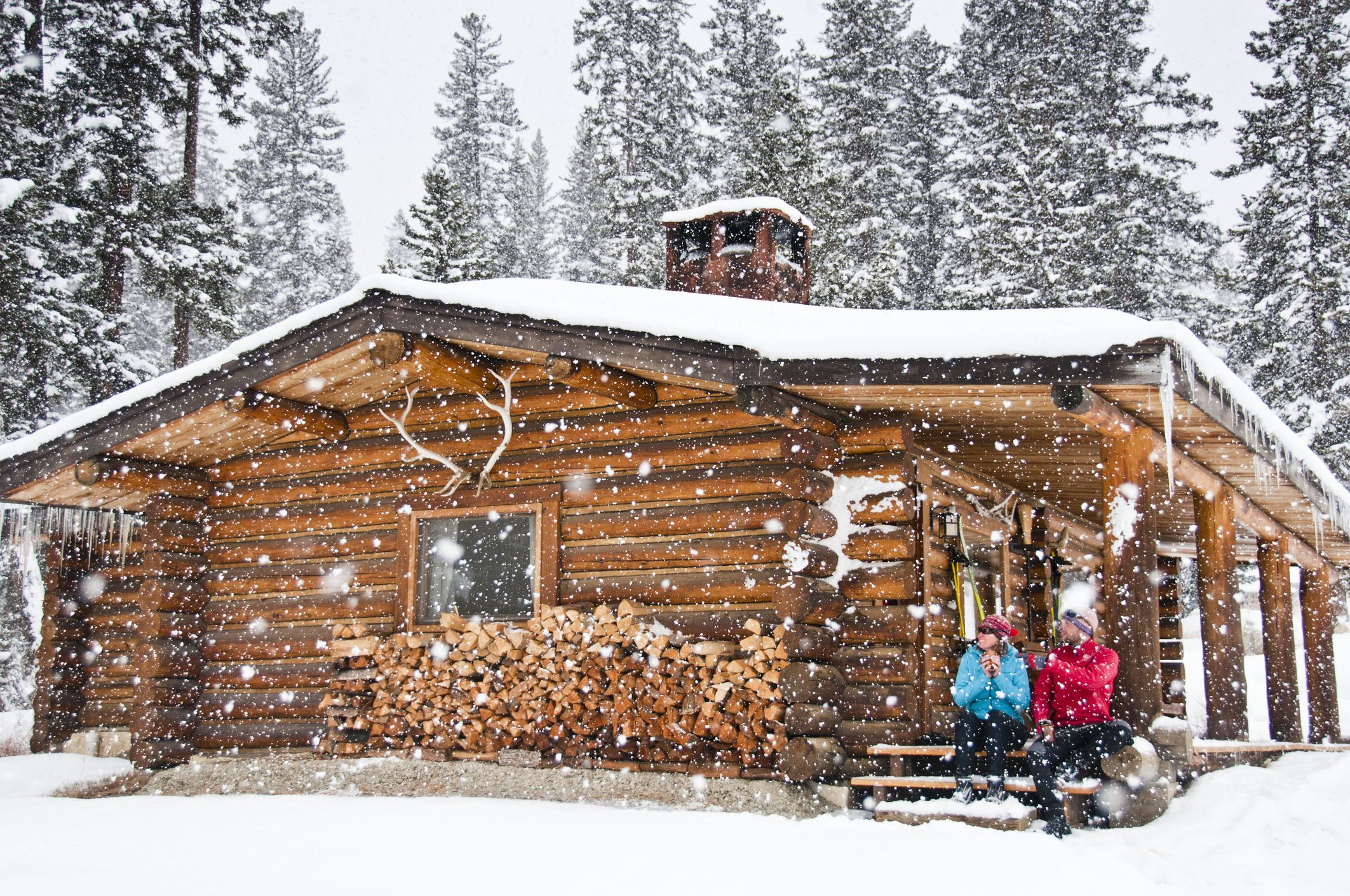 ски бягащи на дървена кабина в падащ сняг