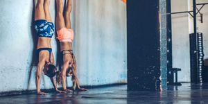 Vrouwen doen handstand in CrossFit box