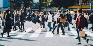 Crowd of busy commuters crossing street in Shibuya crossroad, Tokyo