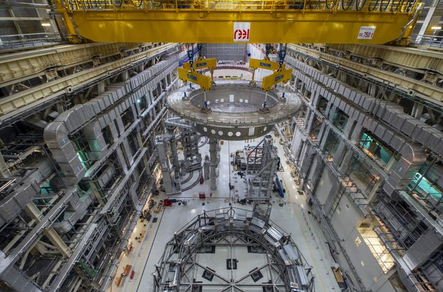 a huge, circular steel base being lifted and transported through iter's tokamak facility