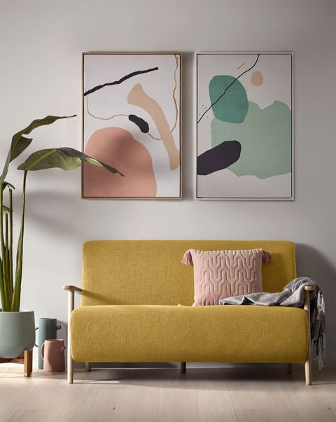 salón con sofá mostaza y dos cuadros de arte abstracto en la pared