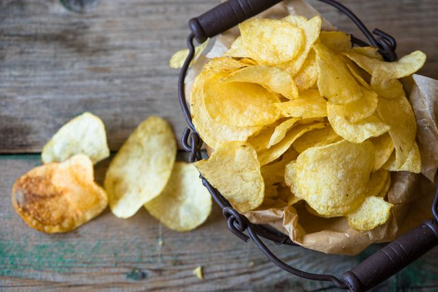 bodegón de patatas fritas de bolsa en una cesta y extendida sobre la mesa un claro ejemplo de comida procesada