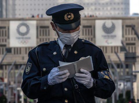 Un policía consulta su libreta mientras se corre el maratón de Tokio.