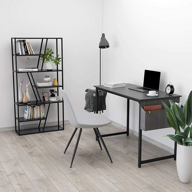 corner of a home office with black bookcase, desk, and a white and black chair