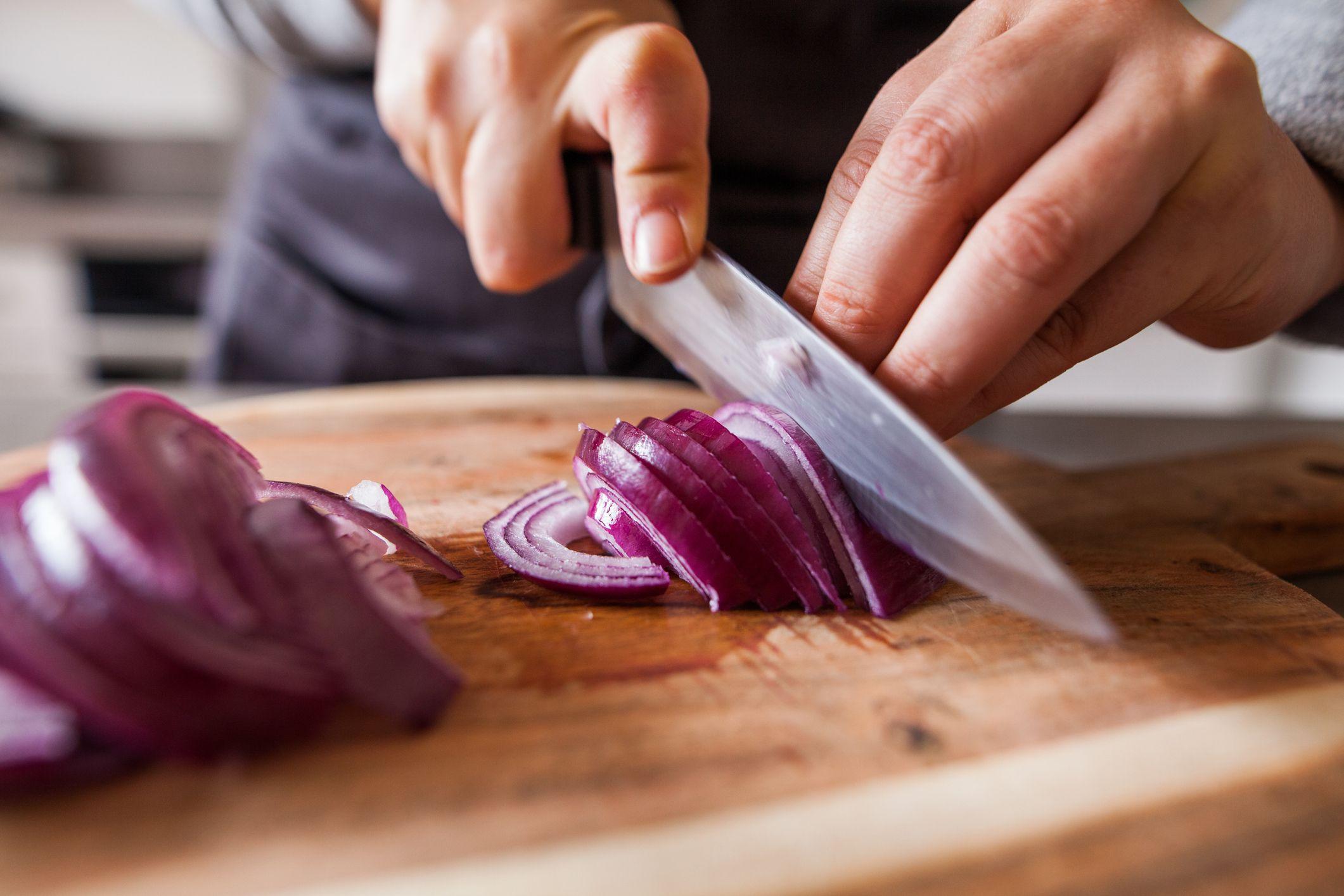 hender som skjærer en rødløk med en kniv
