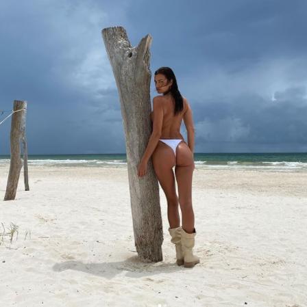 irina shayk posando de espaldas en topless mostrando el culo en la playa apoyada en un árbol