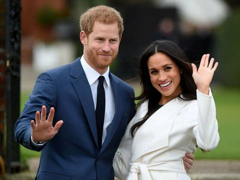 el príncipe harry y  meghan markle de pie saludando y sonriendo