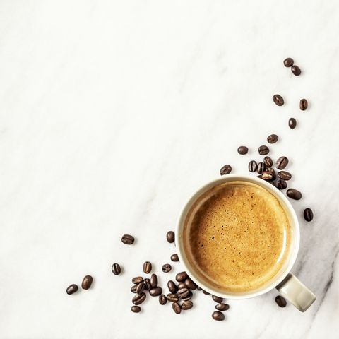A cup of coffee and coffee beans on white, marble background