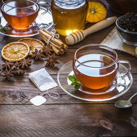 Tea time: cup of tea, cinnamon sticks, anise, dried orange on wooden table