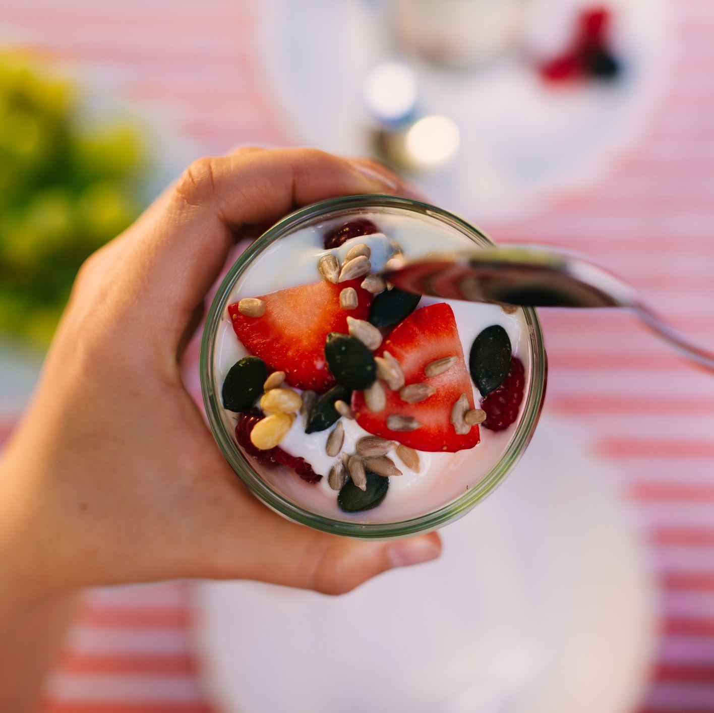 scooping yogurt and berries out of mason jar