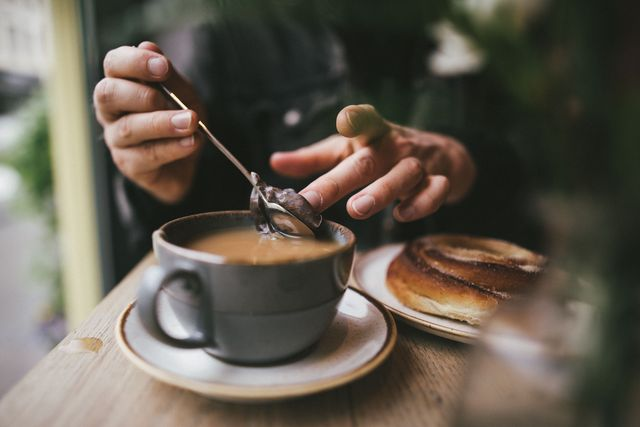 close up of hands and cup, making tea in morning light, having breakfast in a cafe