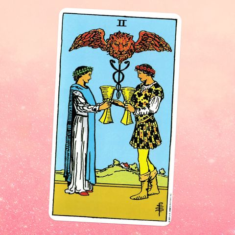 the two of cups tarot card, showing a woman in a white robe and a man in a yellow page outfit facing each other, holding goblets, with a winged lion above them