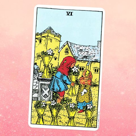 the tarot card the six of cups, showing a person in a red hood and blue tunic handing a cup full of flowers to a person in a yellow and blue dress five more cups filled with flowers surround them