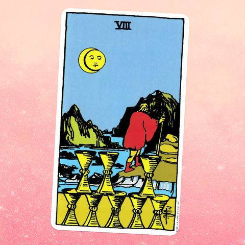 the tarot card the eight of cups, showing a person walking on a hilly shorline, with eight golden cups below them