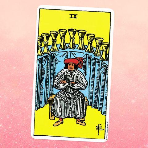 карта таро девятка кубков, изображающая человека в белом халате и красной шляпе, сидящего со скрещенными руками перед высоким столом, на котором размещены девять золотых чаш